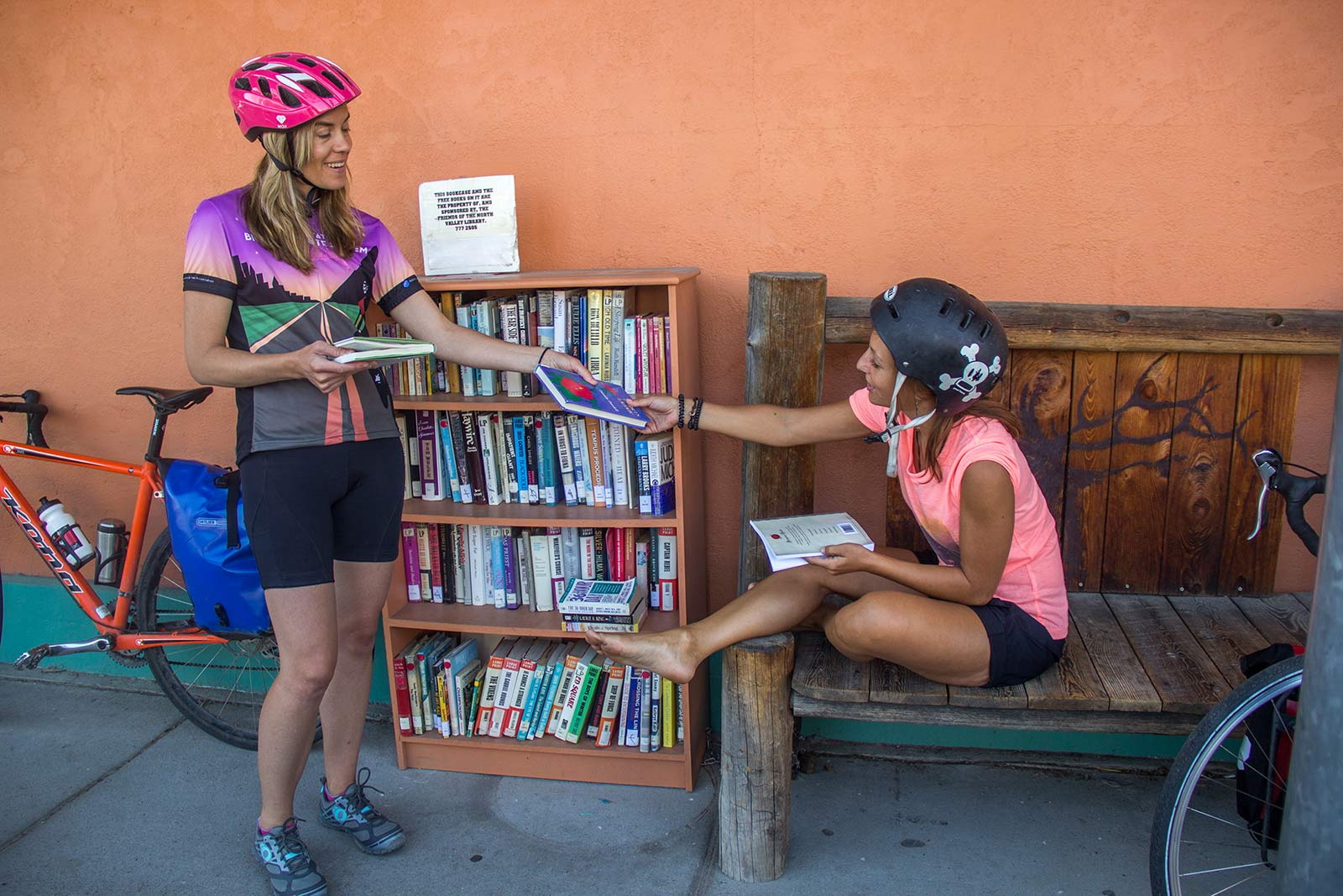 Cyclists look through books during a break from biking the Bitterroot Trail
